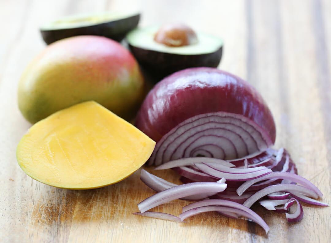 mango, onion, and avocado on cutting board