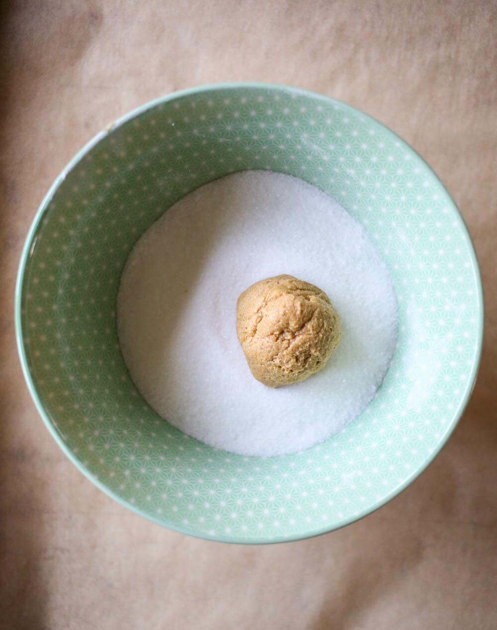 rolling ginger spice cookie dough in sugar
