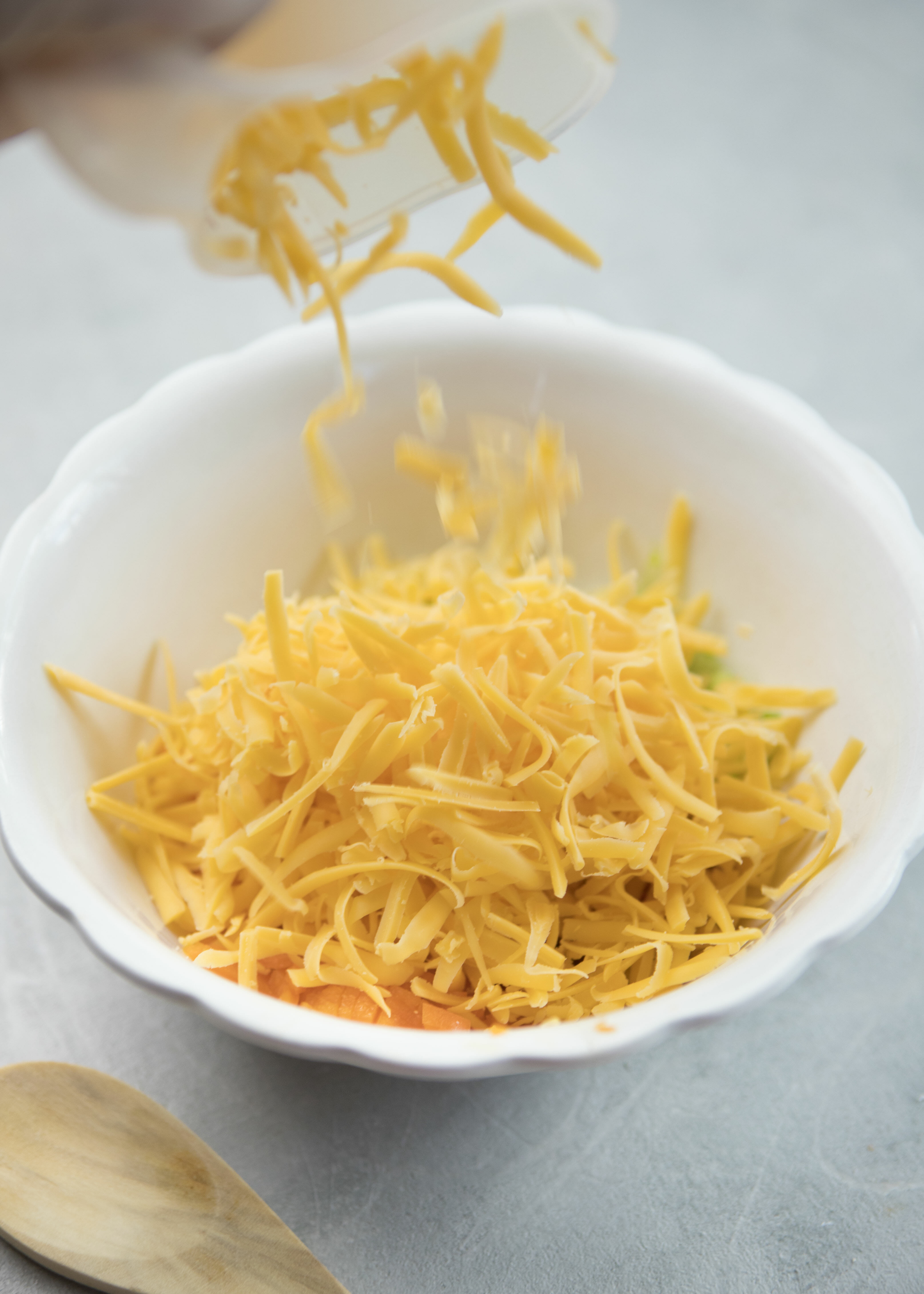 adding shredded cheddar cheese to Perfect Cheeseball