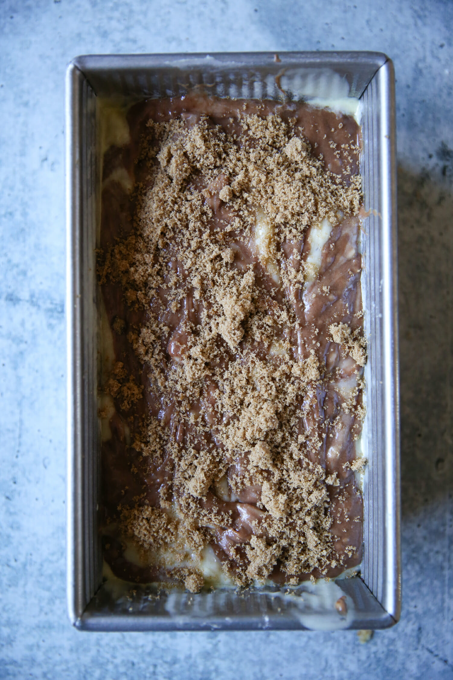 sprinkling brown sugar on chocolate swirled banana bread