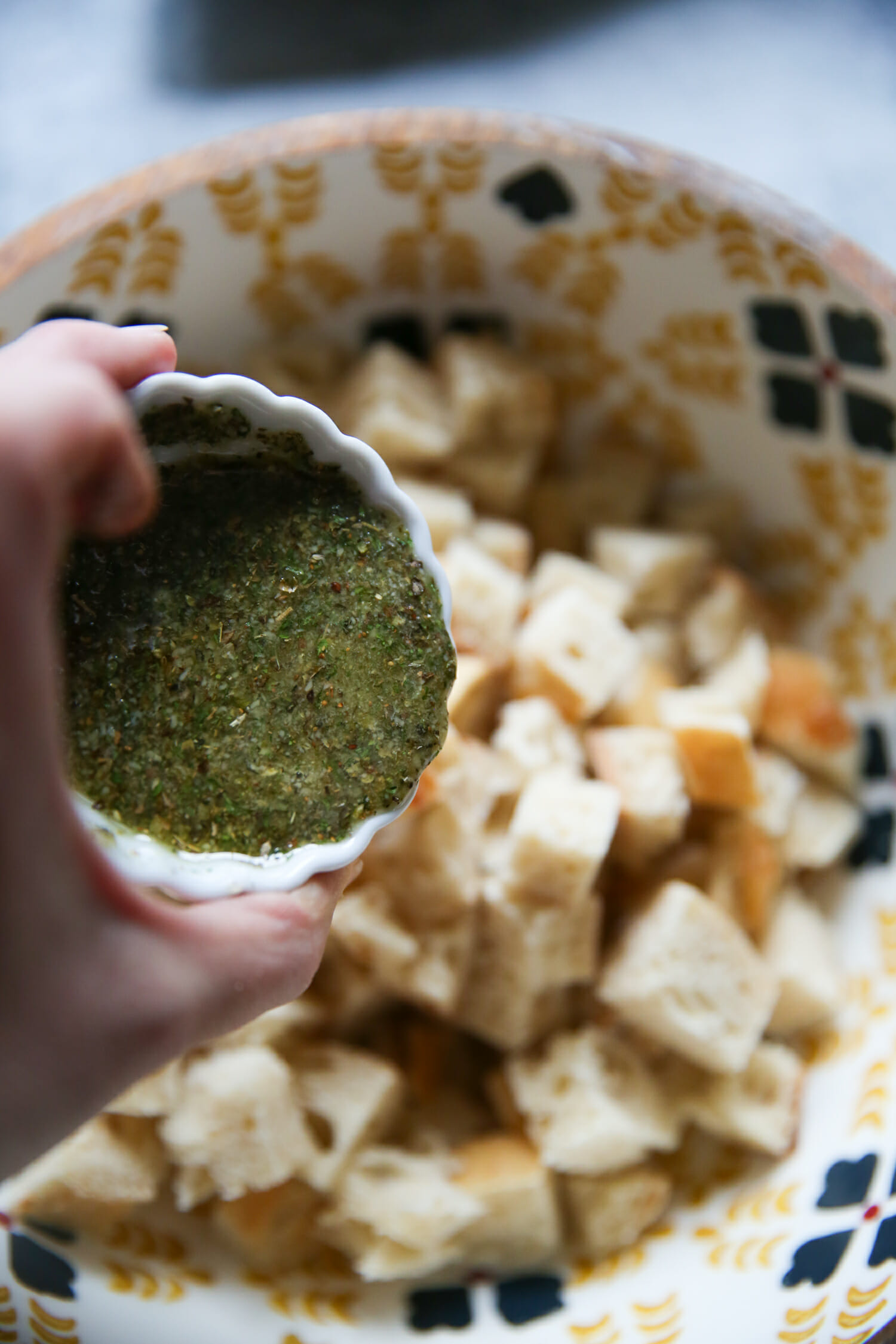 seasoning homemade sourdough garlic-herb croutons from our best bites