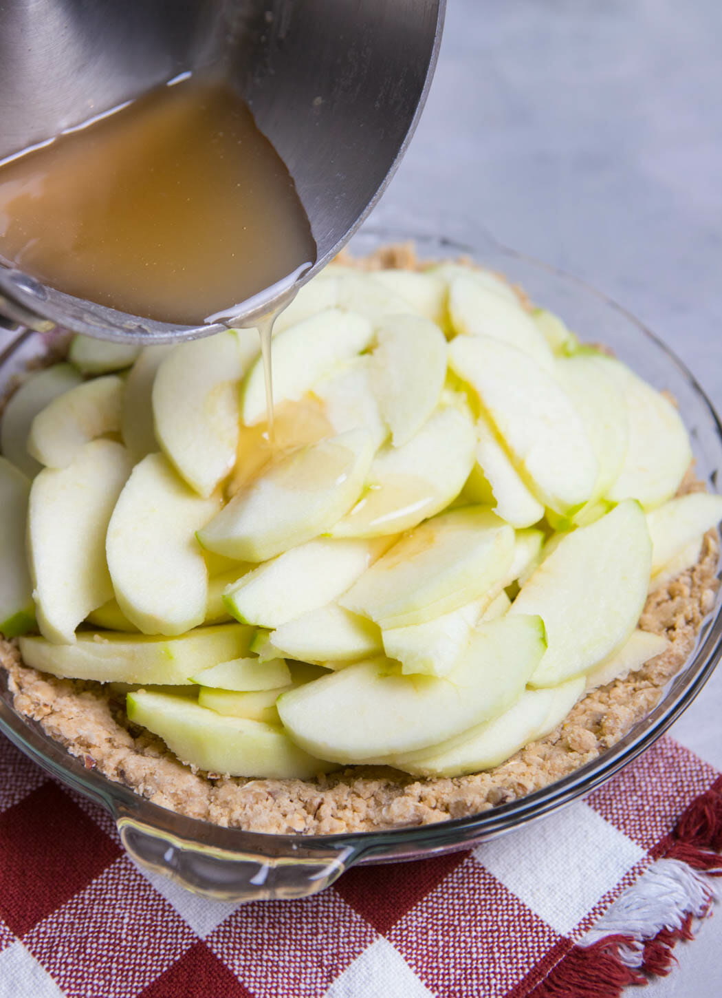 pouring syrup mixture over apples in Crumb Topped Apple Pie from Our Best Bites