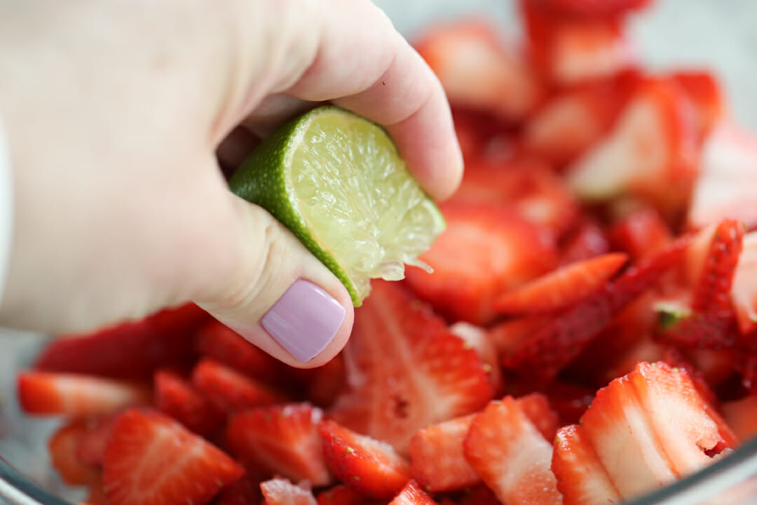 squeezing lime juice in strawberries