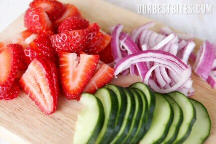 Fresh strawberries, cucumbers, and onions