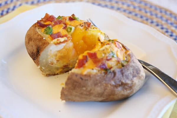 cut stuffed baked potato served on plate