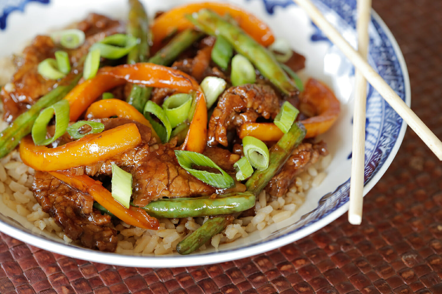 beef and green bean stir fry over rice in a blue bowl with chop sticks