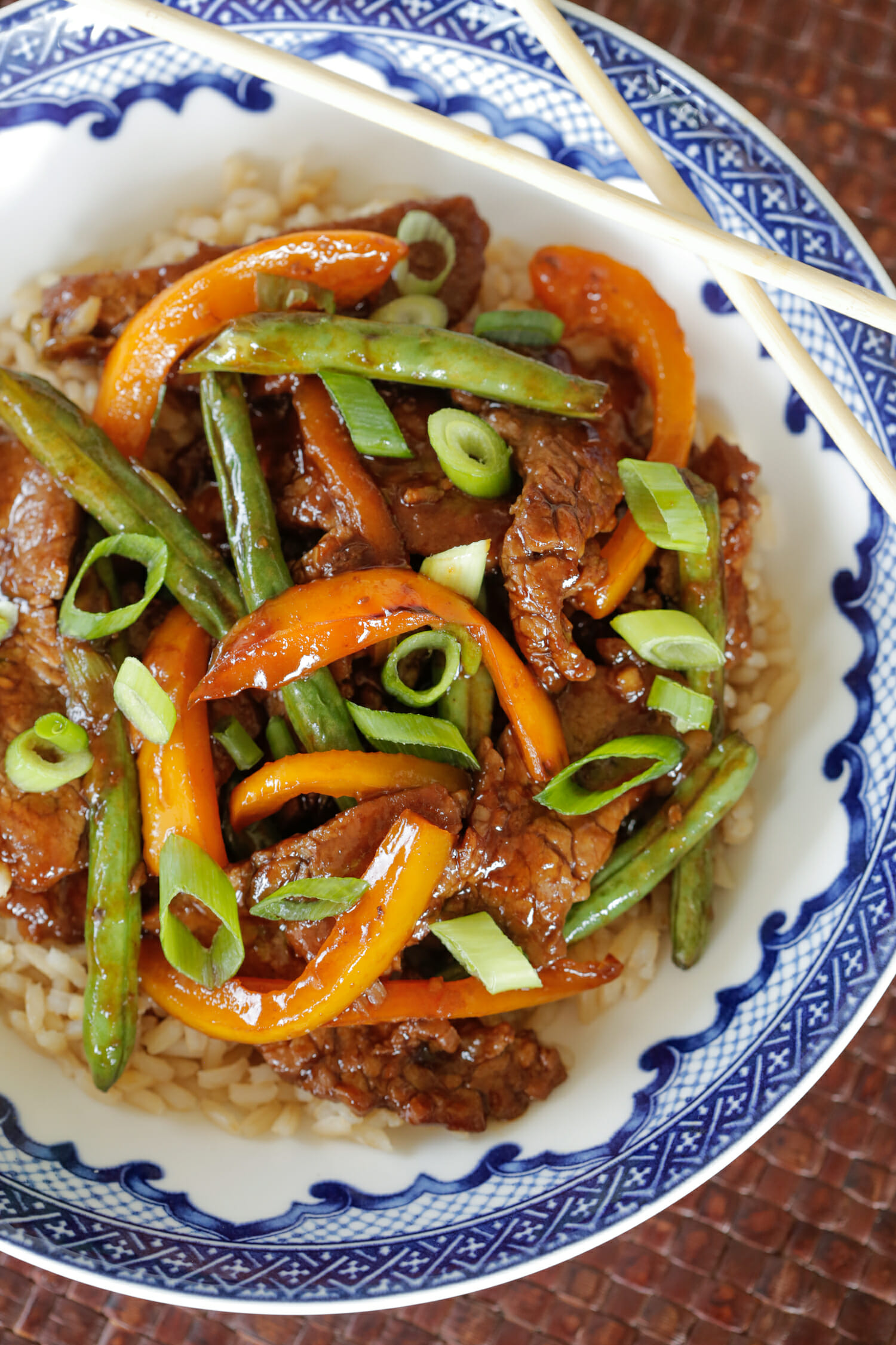 beef and green bean stir fry over rice in a blue bowl with chopsticks