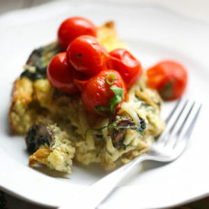 Caramelized Onion Strata on a plate with a fork and tomatoes