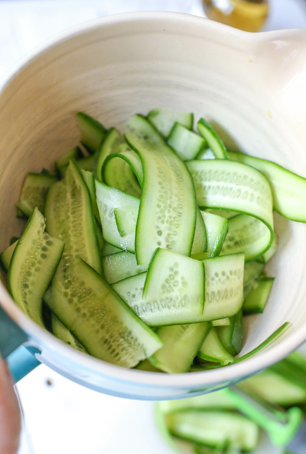 cucumber ribbons in mixing bowl for quick pickles from Our Best Bites