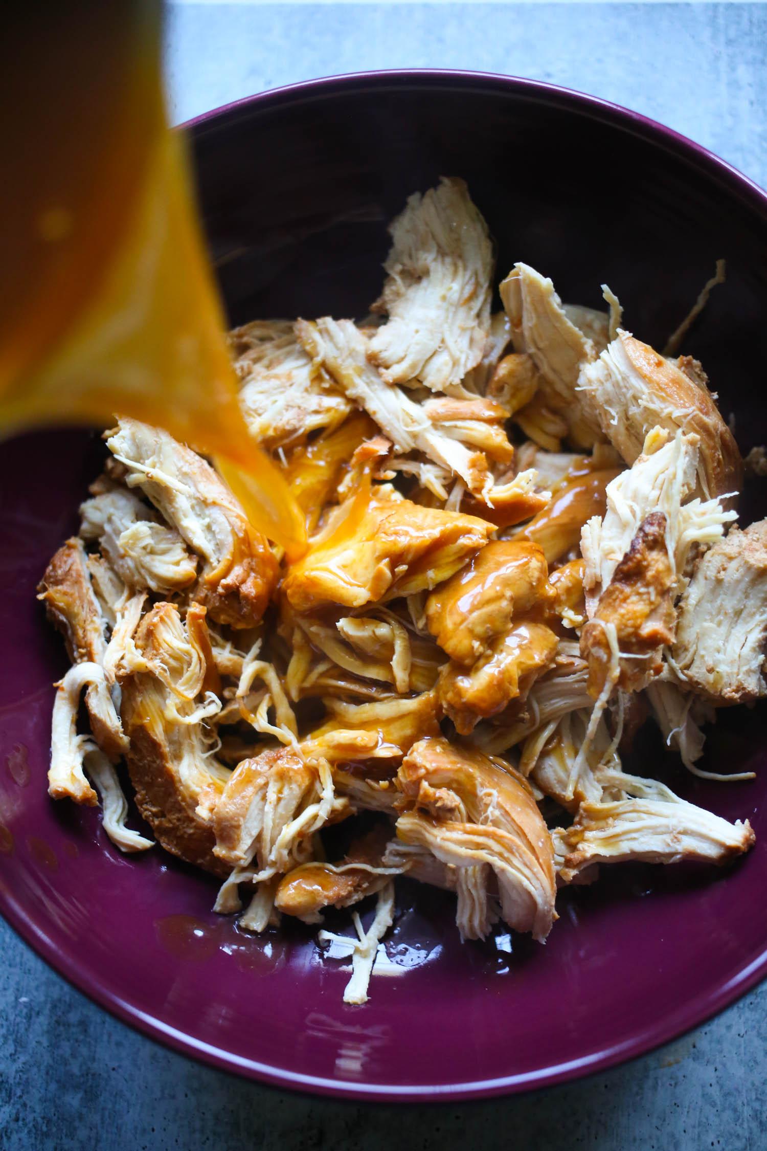 adding sauce to slow cooker honey garlic chicken