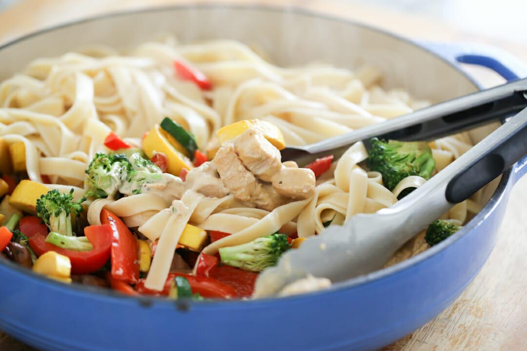 mixing pasta in pan