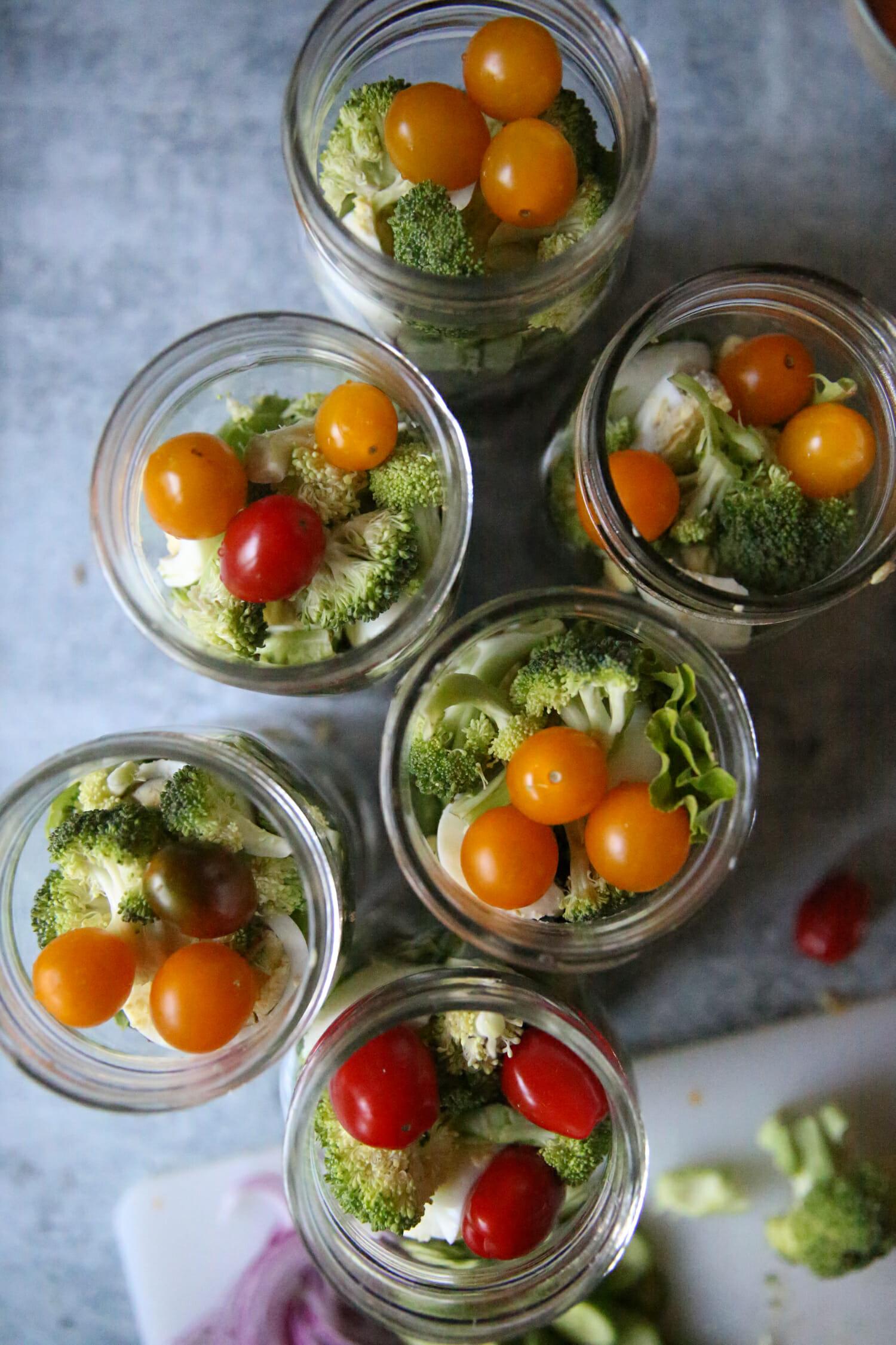 broccoli and tomatoes in salad jars