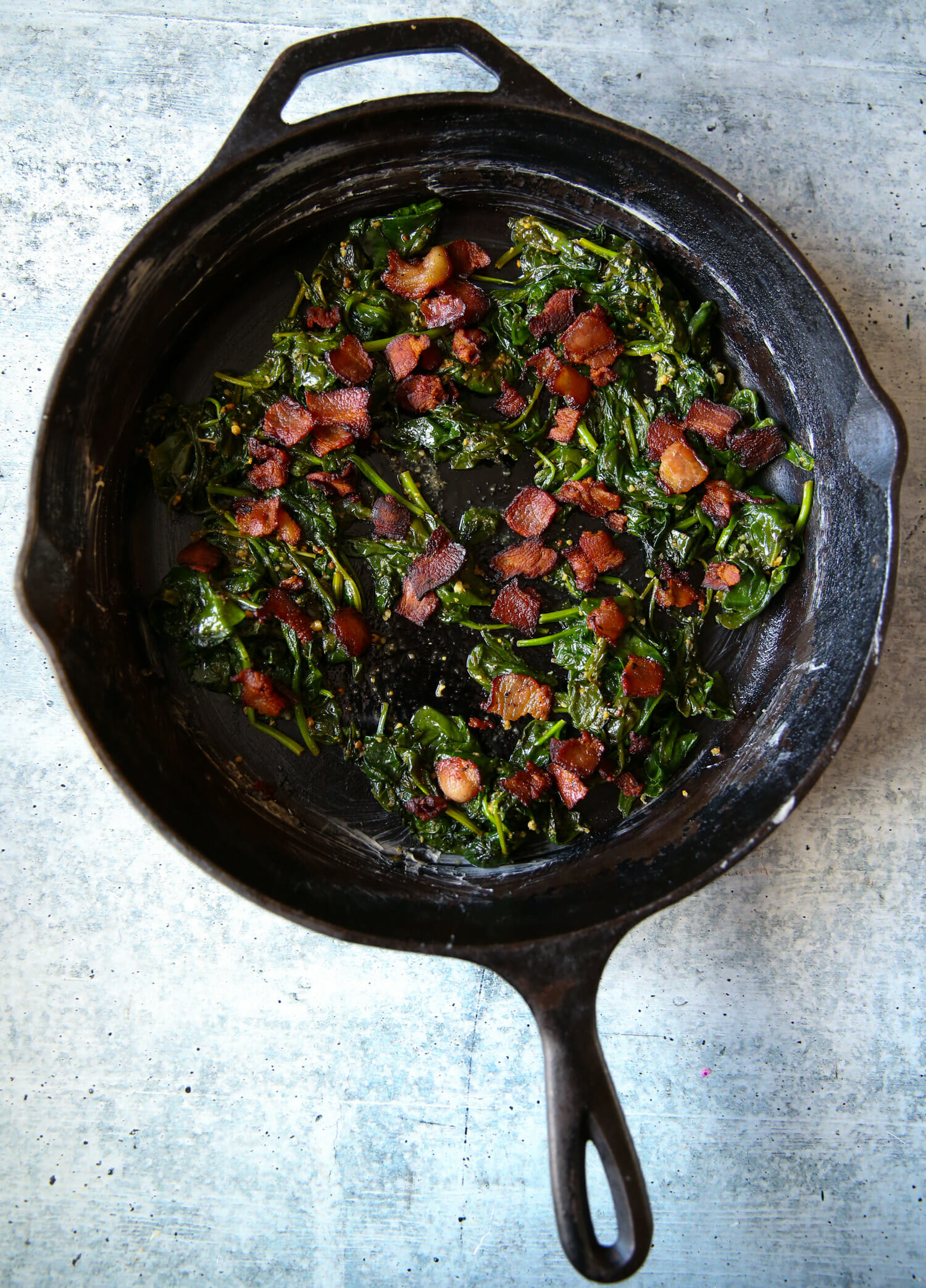 bacon and spinach in a cast iron pan