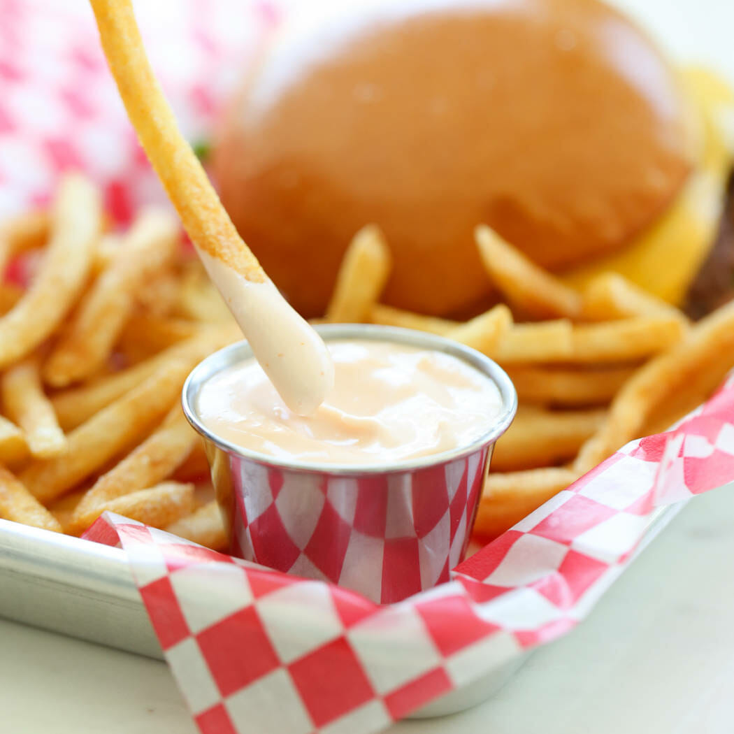 dipping french fry in sauce